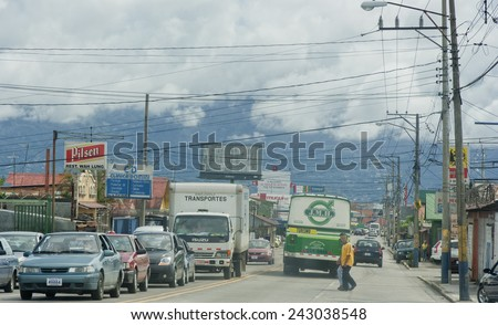 SAN JOSE, COSTA RICA - AUGUST 31, 2008: Traffic jam and crossing people on main street in San Jose, Costa Rica. San Jose is a modern city with bustling commerce and tourism industry. - stock photo