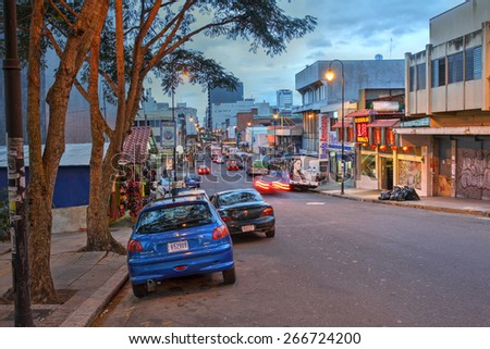 SAN JOSE, COSTA RICA - JANUARY 18: Twilight scene along the Avenida Central from Plaza de la Democracia where the National Musem is located towards the city centre on January 18, 2015. - stock photo