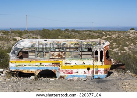 SAN JUAN, ARGENTINA, DEC 4: Detail of rusted old colored school bus with broken windows and clear blue sky abandoned in the countryside in the North of Argentina 2014 - stock photo