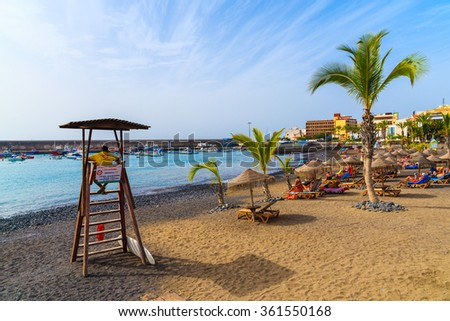 SAN JUAN BEACH, TENERIFE - NOV 15, 2015: Lifeguard tower on tropical beach with palm trees in San Juan town on coast of Tenerife, Canary Islands, Spain.