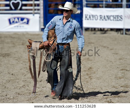 SAN JUAN CAPISTRANO, CA - AUGUST 25: unidentified cowboy carries his saddle in the ring at the PRCA Rancho Mission Viejo rodeo in San Juan Capistrano, CA on August 25, 2012. - stock photo