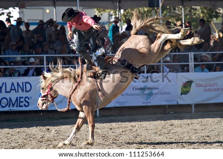 SAN JUAN CAPISTRANO, CA - AUGUST 25: unidentified cowboy competes in the saddle bronc riding event at the PRCA Rancho Mission Viejo rodeo in San Juan Capistrano, CA on August 25, 2012. - stock photo