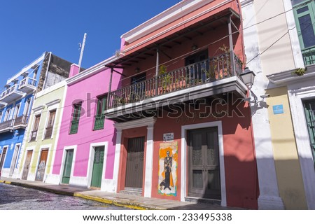 SAN JUAN, PUERTO RICO - JANUARY 29, 2014: Brightly colored colonial style buildings flank the cobblestone street of San Sebastian in historical Old San Juan - stock photo