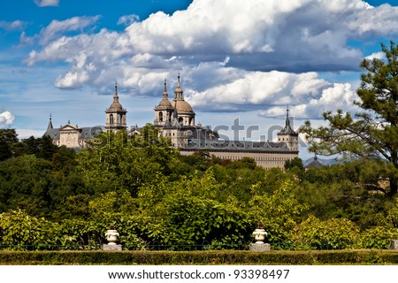 San Lorenzo de El Escorial Monastery from Casita del Infante. The towers of the church and monastery are set of by a bright blue sky.