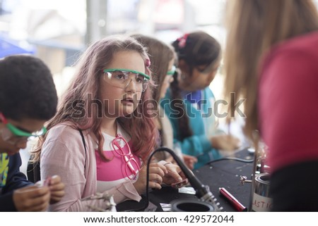 SAN MATEO, CA May 20 2016 - A group of girls working with electronics at the 'Learn to Solder' activity station presented by Google at the 11th Annual Bay Area Maker Faire.