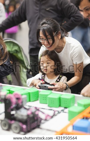 SAN MATEO, CA May 20 2016 - A woman helps a child drive a small robot during the 11th annual Bay Area Maker Faire at the San Mateo County Event Center. - stock photo