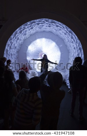 SAN MATEO, CA May 20 2016 - A woman poses in an art sculpture in the Dark Room at the 11th Annual Bay Area Maker Faire at the San Mateo County Event Center. - stock photo