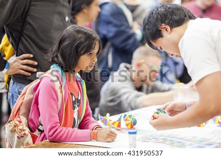 SAN MATEO, CA May 20 2016 - A yong girl receives instructions for a craft project during the 11th annual Bay Area Maker Faire at the San Mateo County Event Center.