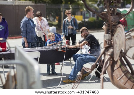 SAN MATEO, CA May 20 2016 - A young boy operates an interactive art piece during the 11th Annual Bay Area Maker Faire at the San Mateo County Event Center. - stock photo