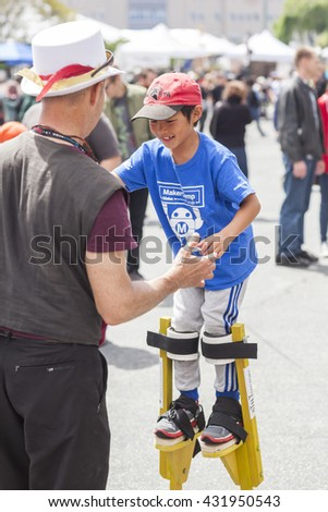 SAN MATEO, CA May 20 2016 - A young child receives stilt lessons during the 11th annual Bay Area Maker Faire at the San Mateo County Event Center.