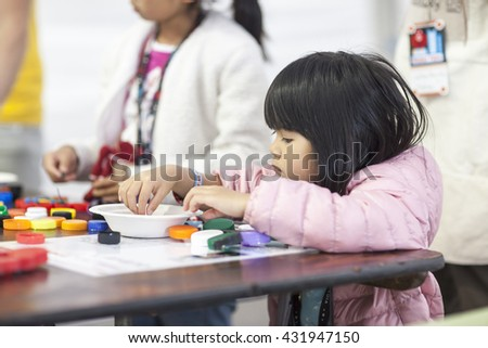 SAN MATEO, CA May 20 2016 - A young girl assembles a crafting project during the 11th Annual Bay Area Maker Faire at the San Mateo County Event Center. - stock photo
