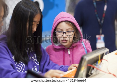 SAN MATEO, CA May 20 2016 - A young girl looks on while her friend uses a computer during the 11th annual Bay Area Maker Faire at the San Mateo County Event Center. - stock photo