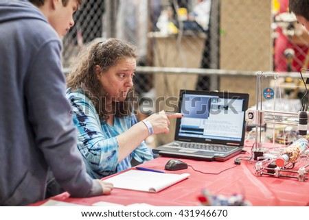 SAN MATEO, CA May 20 2016 - An attendee discusses a device during the 11th annual Bay Area Maker Faire at the San Mateo County Event Center.