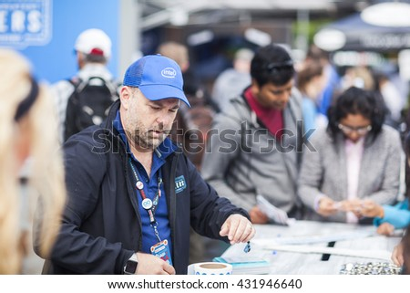 SAN MATEO, CA May 20 2016 - Staff at the Intel sponsor booth assist attendees with activities at the Intel area during the 11th annual Bay Area Maker Faire at the San Mateo County Event Center. - stock photo
