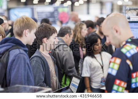 SAN MATEO, CA May 20 2016 - Two teens watch a demonstration of Tinkercad during the 11th annual Bay Area Maker Faire at the San Mateo County Event Center. - stock photo