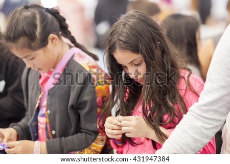 SAN MATEO, CA May 20 2016 - Two young girls work on a craft project during the 11th Annual Bay Area Maker Faire at the San Mateo County Event Center. - stock photo