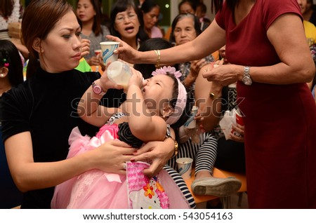 SAN PABLO CITY, LAGUNA, PHILIPPINES - DECEMBER 22, 2016: Candid shot obese baby girl in pink gown bottle feeding having tantrum in the middle of birthday party celebration