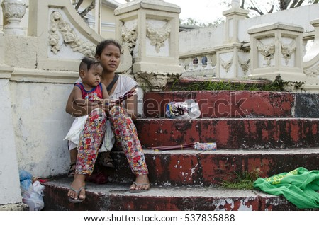 SAN PABLO CITY, LAGUNA, PHILIPPINES - DECEMBER 9, 2016: Mother cuddling baby son at church yard patio selling candles as a means of basic support
