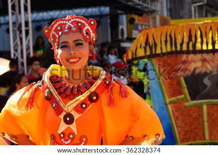 SAN PABLO CITY, LAGUNA, PHILIPPINES - JANUARY 13, 2016: a group of carnival dancers in various costumes dance along the road during the 21st annual coconut festival cultural celebration.