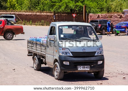SAN PEDRO DE ATACAMA, CHILE - NOVEMBER 17, 2015: Small grey chinese flat-bed truck drives in the gravel town street. - stock photo