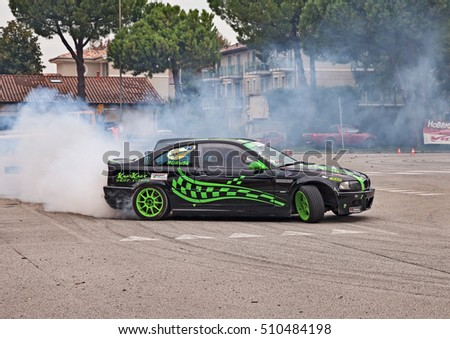 "SAN PIETRO IN VINCOLI, RA, ITALY - OCTOBER 23: crew on a drift racing car BMW in action drifting with smoking tires  in ""Telethon Motor Show"" on October 23, 2016 in San Pietro in Vincoli, RA, Italy"