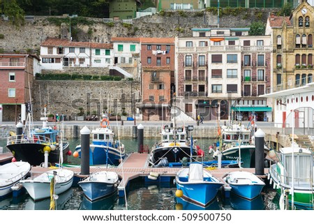 SAN SEBASTIAN, SPAIN  - SEPTEMBER 29. Picturesque houses. Fishing boats and sport fishing boats to recreational boat fishing are moored in the harbor of Donostia San Sebastian on September 29, 2016