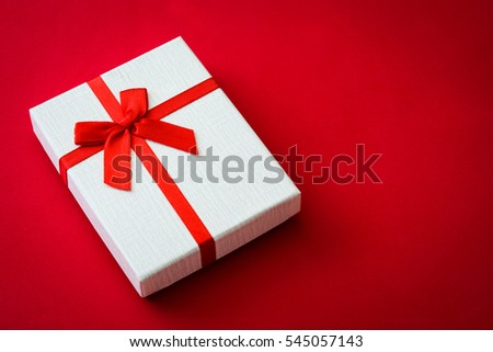 San Valentine white gift box on red background.Love concept Copyspace.