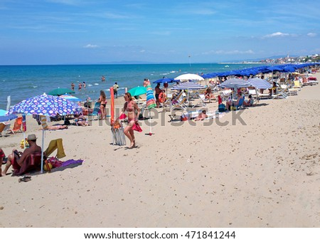 SAN VINCENZO, ITALY - NOVEMBER 01, 2012: Mediterranean beach with people lying on the sand and swimming in the sea. Space at the bottom for copy.