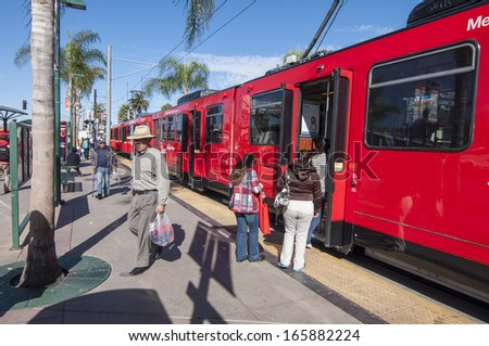 SAN YSIDRO, USA - NOVEMBER 27, 2013: Passengers board the San Diego blue line trolley at the southernmost station stop at the US - Mexico border crossing in San Ysidro on November 27, 2013.