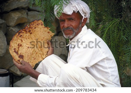 SANA'A,YEMEN-APRIL 13,2012;  Portrait of a baker with traditional bread in Yemen. Baked crust. April 13, 2012 Sana'a, Yemen - stock photo