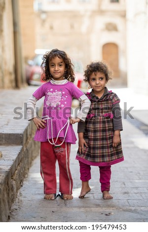 SANA'A, YEMEN - JAN 11, 2014: Unidentified Yemeni girls play in the street in Sana'a. Children of Yemen grow up without education