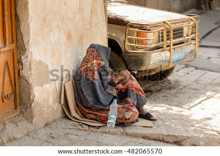 SANA'A, YEMEN - JAN 11, 2014: Unidentified Yemeni woman sits in the street. People of Yemen suffer of poverty due to the unstable political and poor economical situation