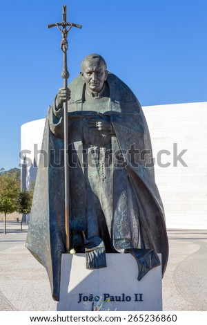 Sanctuary of Fatima, Portugal, March 07, 2015 - Statue of Pope John Paul II with the Basilica of Most Holy Trinity in background. Fatima is one of the most important pilgrimage locations for Catholics - stock photo