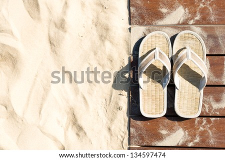 Sand and beige flip flops. Pair of sandals on boardwalk. Walk on sand in bright sunny day, Leisure time at beach. Creative concept of carefree vacations. Popular outdoor activity in summer. - stock photo