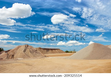 Sand and gravel quarry construction site with cloudy blue sky