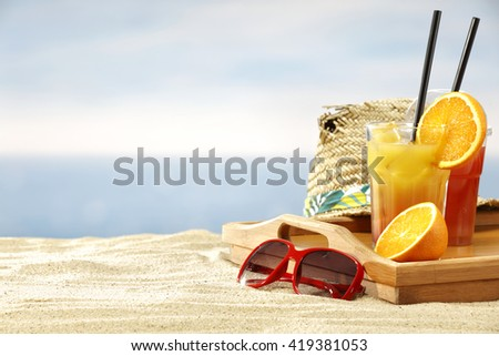sand and hat and orange juice