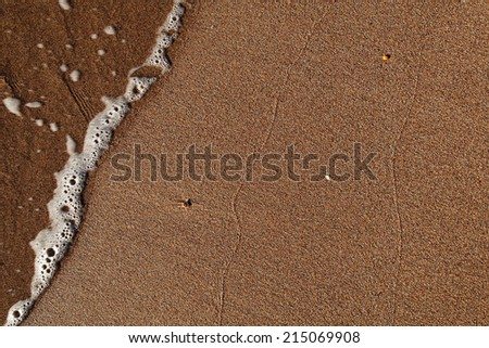 Sand and the sea foam wave as background. - stock photo