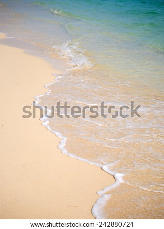 Sand and wave on the beach - stock photo