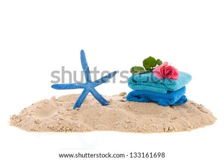 Sand at the beach with towels and starfish - stock photo