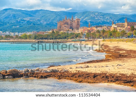 Sand beach in Palma de Mallorca, gothic cathedral in background, Spain - stock photo
