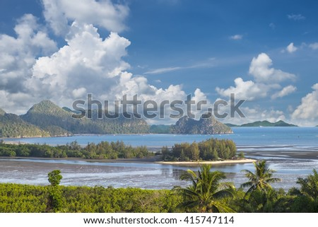 Sand beach surround by mangrove forest and mountain with clouds and blue sky at Tungmaha bay, Chumporn, Thailand.