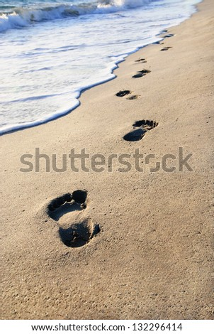 sand beach, wave and footsteps at sunset time - stock photo