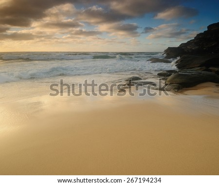 Sand beach with soft and smooth water and clouds and some rocks and with wide sand line - stock photo