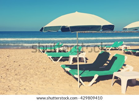 Sand beach with sun umbrella and green lounges. Summertime or vacation theme. Toned colors vintage photo
