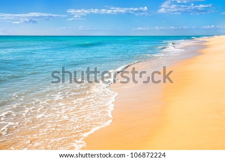 Sand beach with surf water background - stock photo