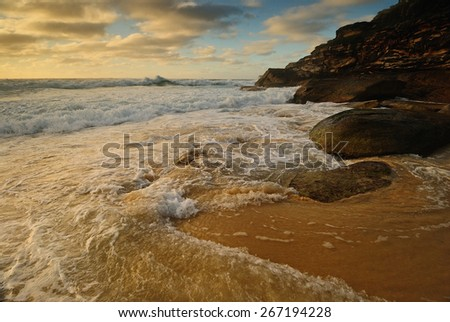 Sand beach with wavy water and clouds and some rocks and with wide sand line - stock photo