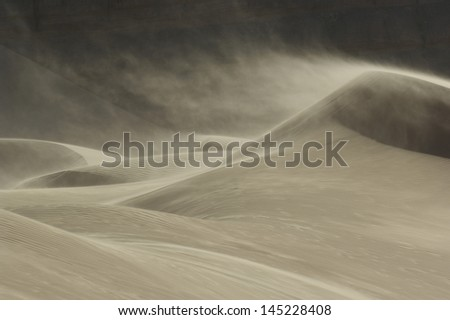 Sand blowing over sand dune in wind - stock photo
