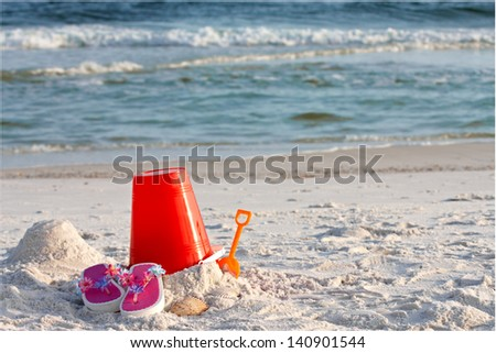 Sand bucket, shovel and flip flops in the sand at the beach.