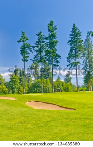 Sand bunker on the beautiful golf course in a bright sunny day. - stock photo