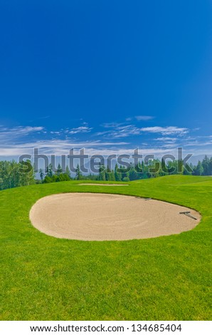 Sand bunker on the beautiful golf course in a bright sunny day.